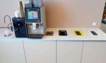 """""""Puhastusimport"""" biuro kavos pertraukėlės kampelyje angos pažymėtos spalvų kodais ir piktogramomis"""